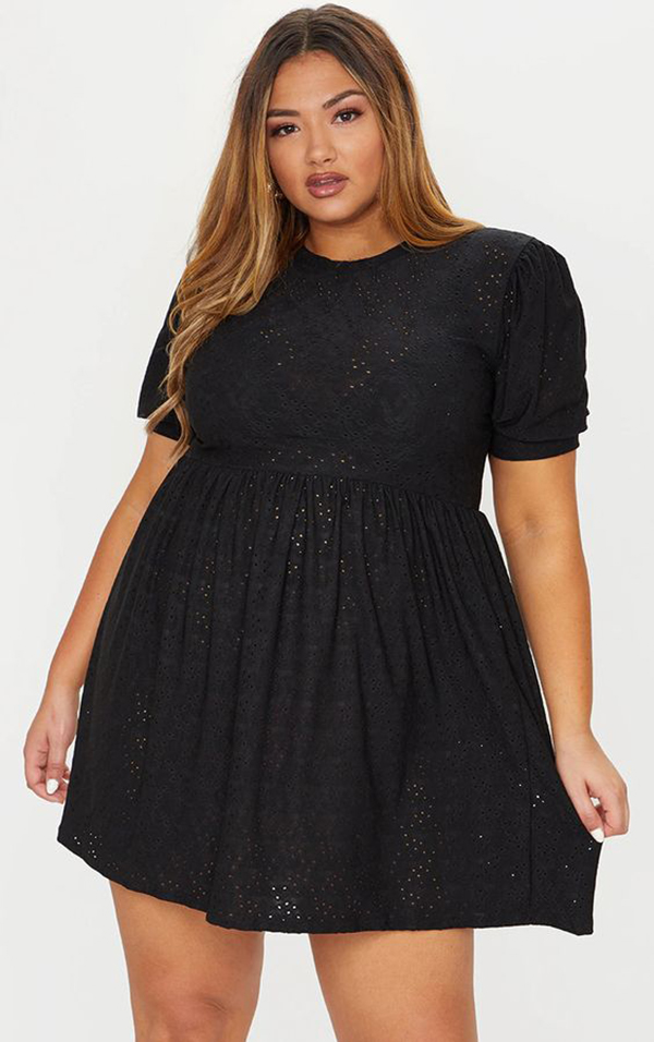 A plus-size model wearing a black babydoll dress.