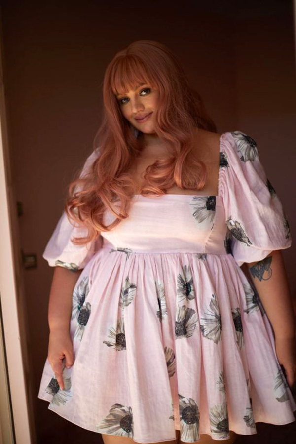 A plus-size model wearing a floral babydoll dress.