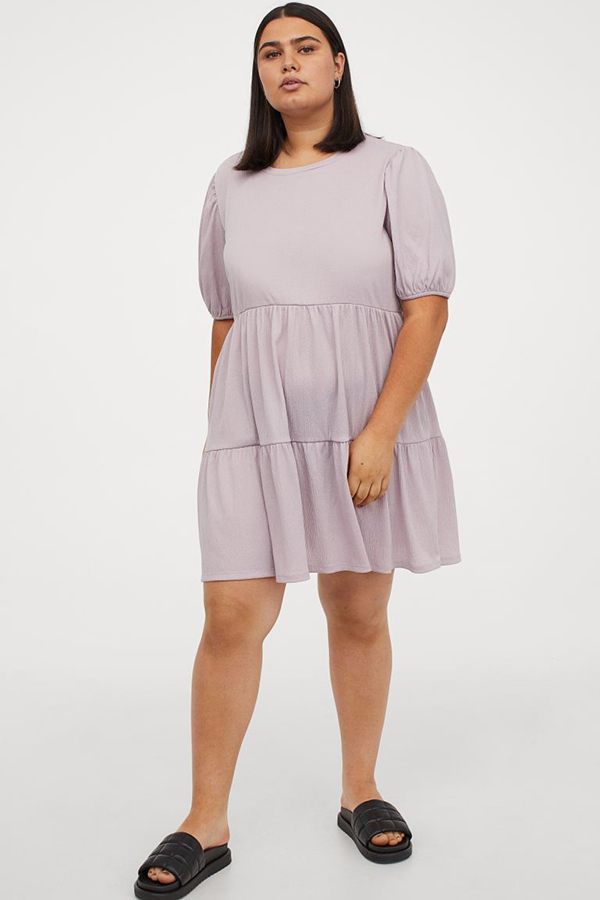 A plus-size model wearing a lavender babydoll dress.
