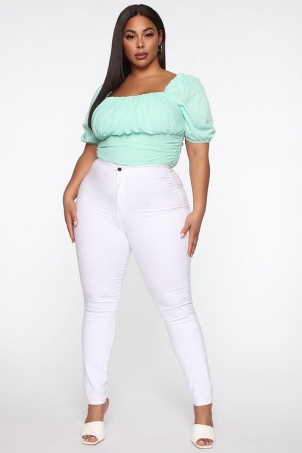 A plus-size model wearing an aqua bustier top.
