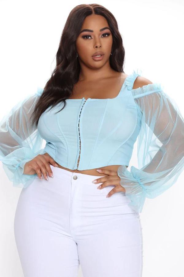 A plus-size model wearing a light blue bustier top.