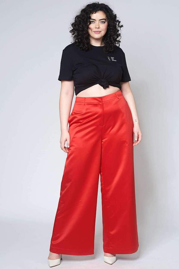 A woman wearing a black top and red flare pants.
