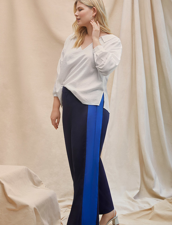 A woman wearing a white top and black and blue stripe flare pants.