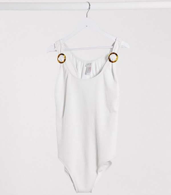 A white plus-size one-piece swimsuit hanging on a hanger.
