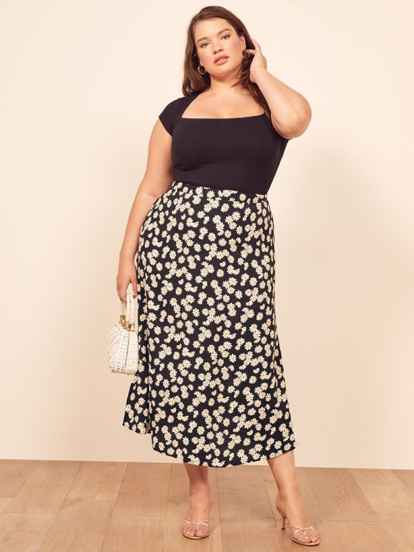 A plus-size model wearing a floral satin slip skirt.