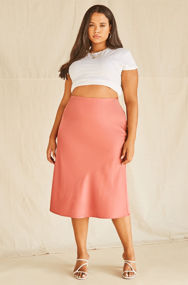 A plus-size model wearing a coral satin slip skirt.