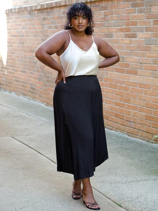 A plus-size model wearing a black satin slip skirt.