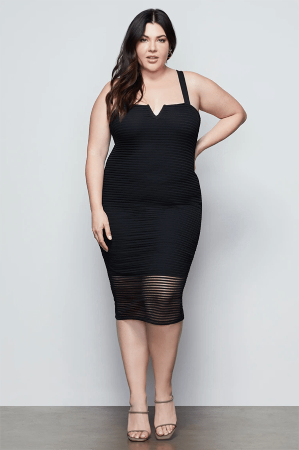 A plus-size model wearing a black fitted midi dress.