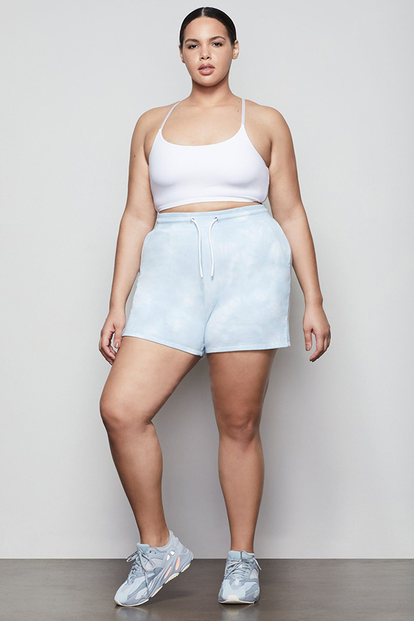 A plus-size model wearing blue and white tie-dye sweat shorts.