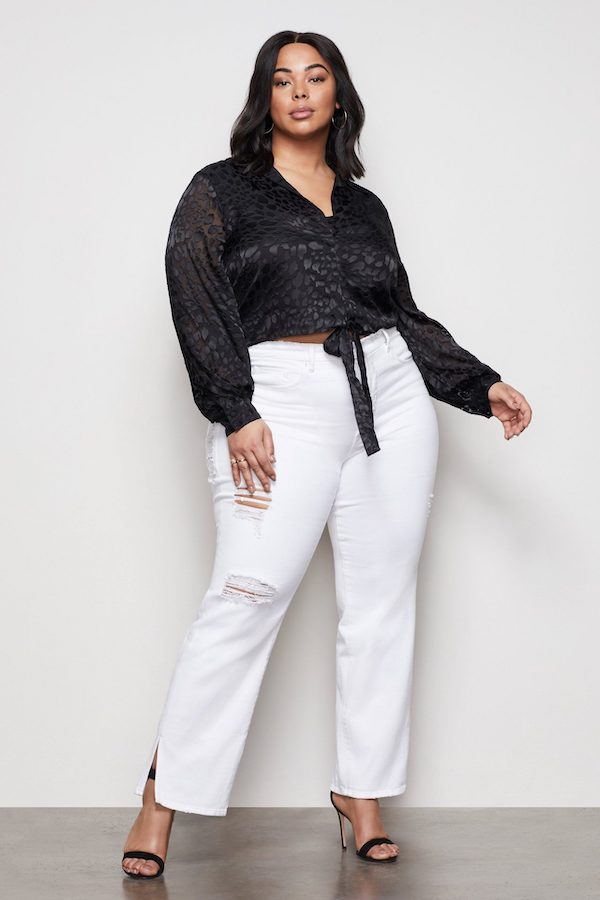 A woman wearing and black top a white jeans.