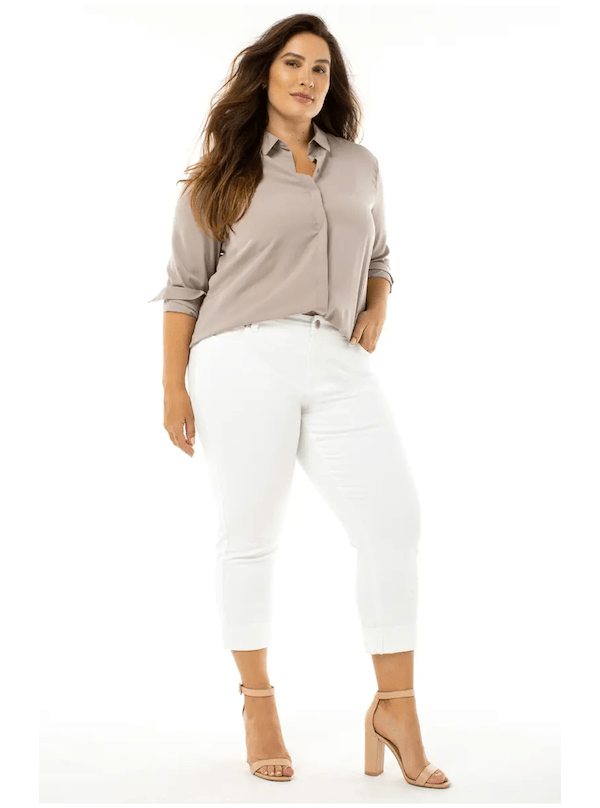 A woman wearing a tan top and white jeans.