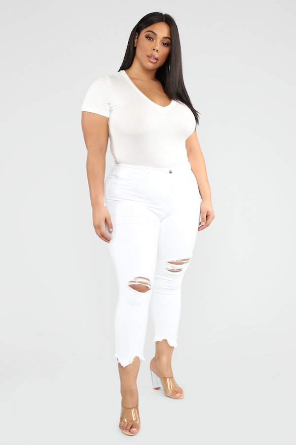 A woman wearing a white tee and white ripped jeans.