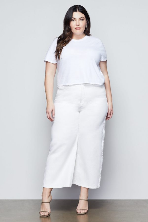 A woman wearing a white tee and wide leg white jeans.