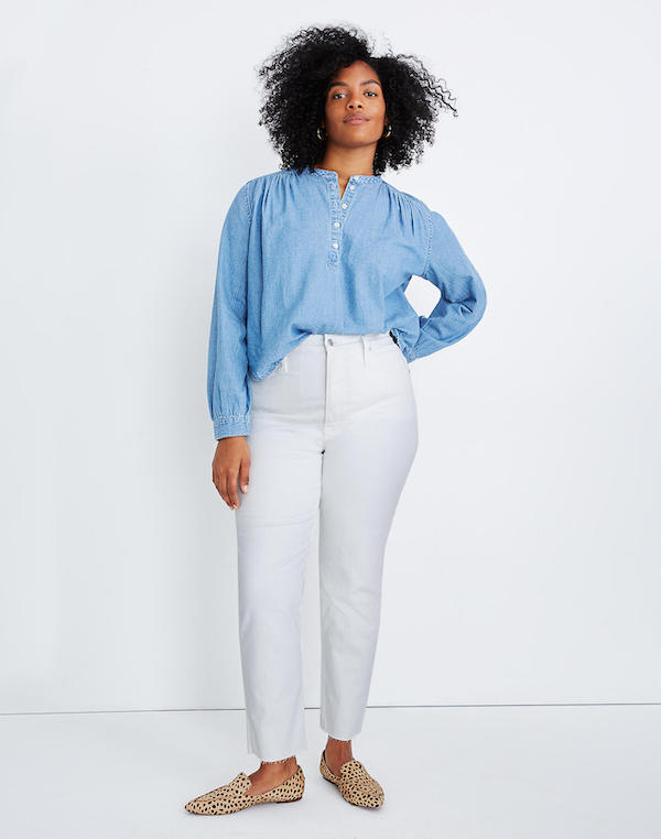A woman wearing a blue denim top and white jeans.