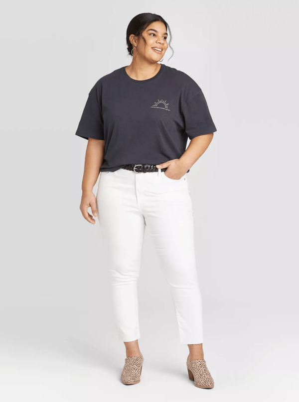 A woman wearing a black t-shirt and white jeans.