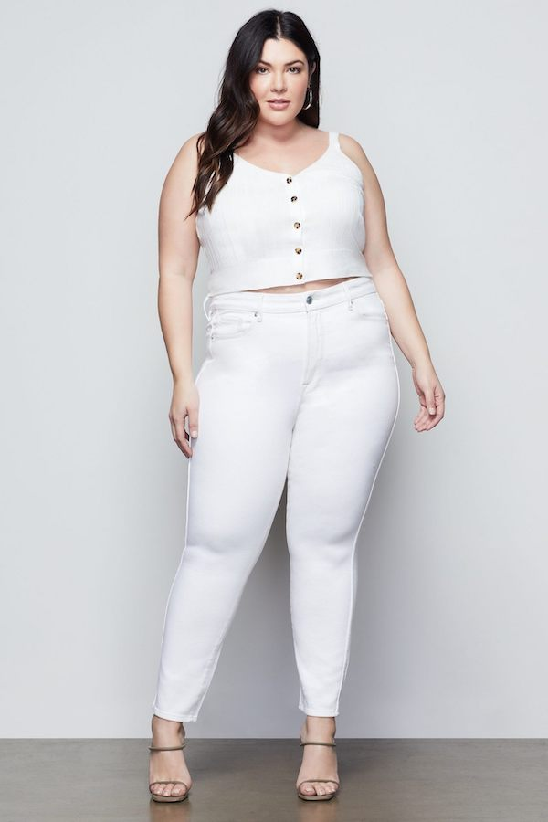 A woman wearing a white cami and white jeans.