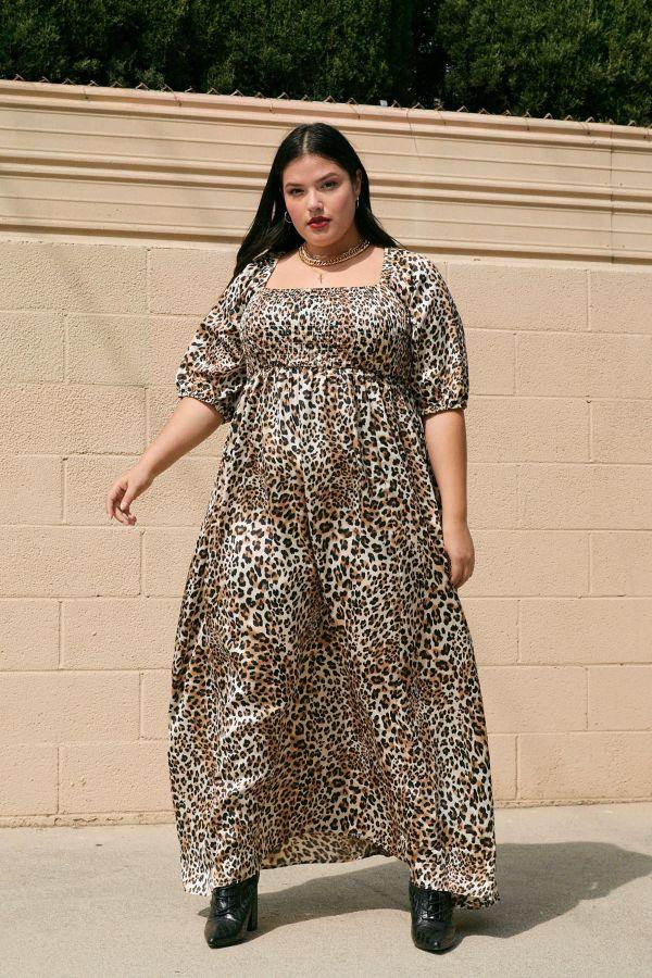 A woman wearing a plus-size animal print maxi dress.