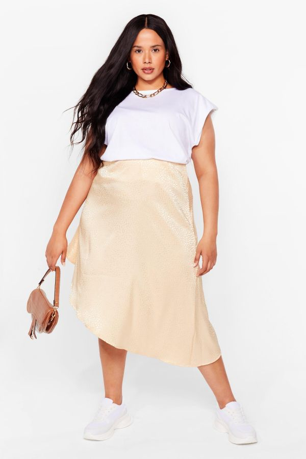 A woman wearing a white t-shirt and plus-size cream satin skirt.