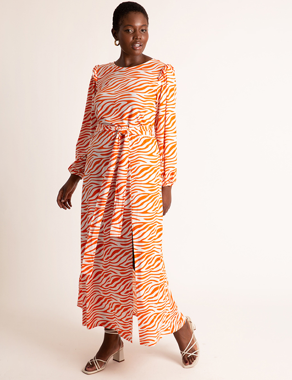 A plus-size model wearing an orange printed dress, which is now on sale at Eloquii for less than $39.