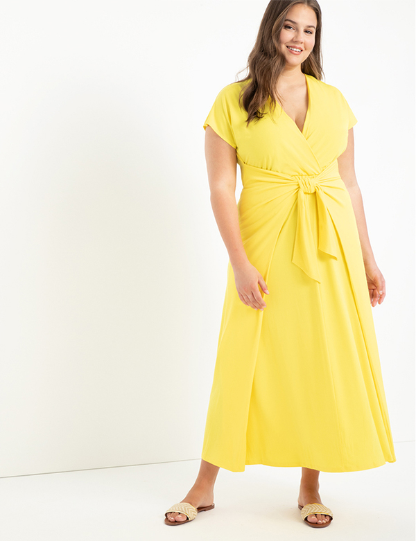 A plus-size model wearing a yellow dress, which is now on sale at Eloquii for less than $39.
