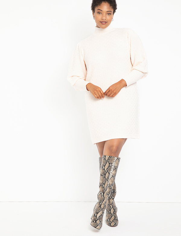 A plus-size model wearing a white sweater dress, which is now on sale at Eloquii for less than $39.