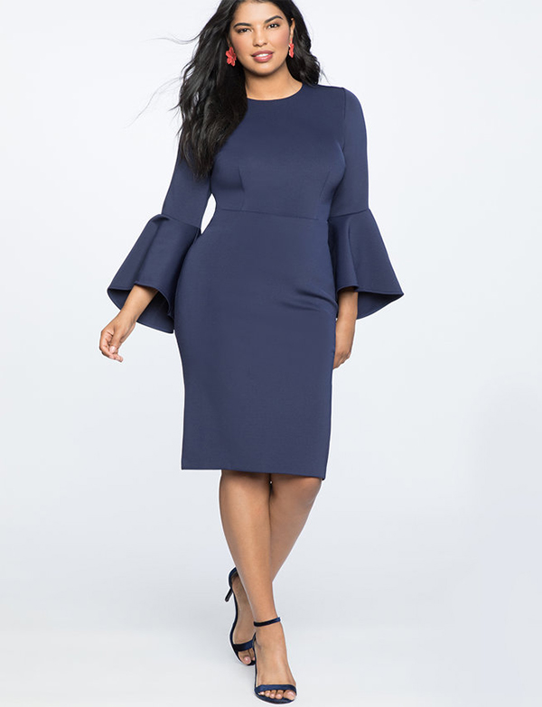 A plus-size model wearing a navy cocktail dress, which is now on sale at Eloquii for less than $39.