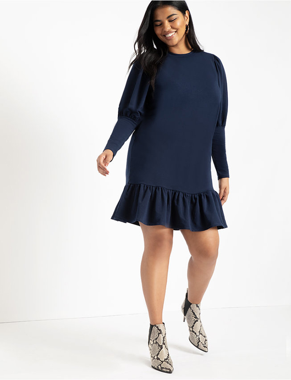 A plus-size model wearing a navy sweatshirt dress, which is now on sale at Eloquii for less than $39.