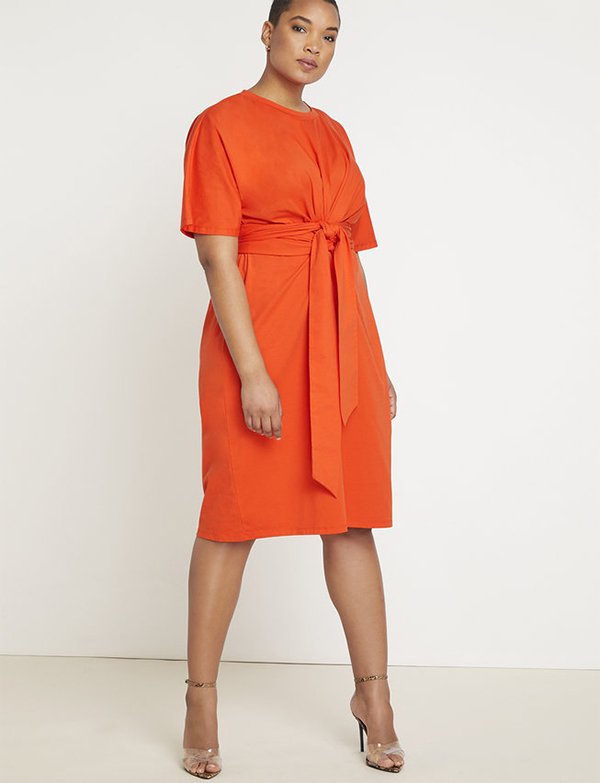 A plus-size model wearing and orange dress, which is now on sale at Eloquii for less than $39.