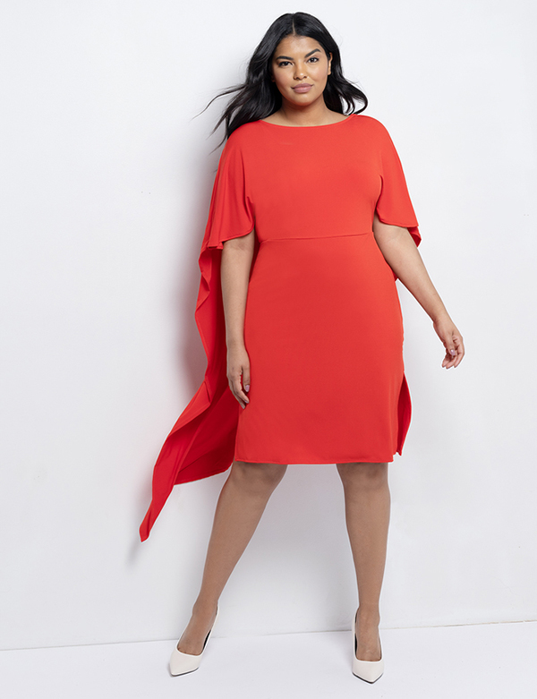 A plus-size model wearing a red cape dress, which is now on sale at Eloquii for less than $39.