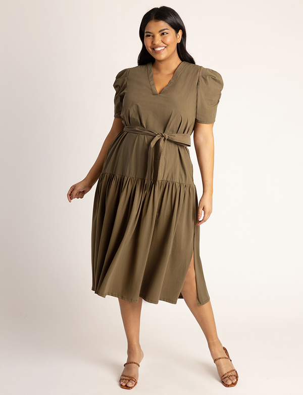 A plus-size model wearing an olive green dress, which is now on sale at Eloquii for less than $39.