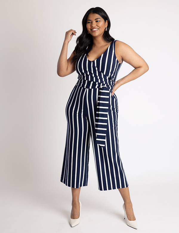 A plus-size model wearing a navy striped jumpsuit, which is now on sale at Eloquii for less than $49.
