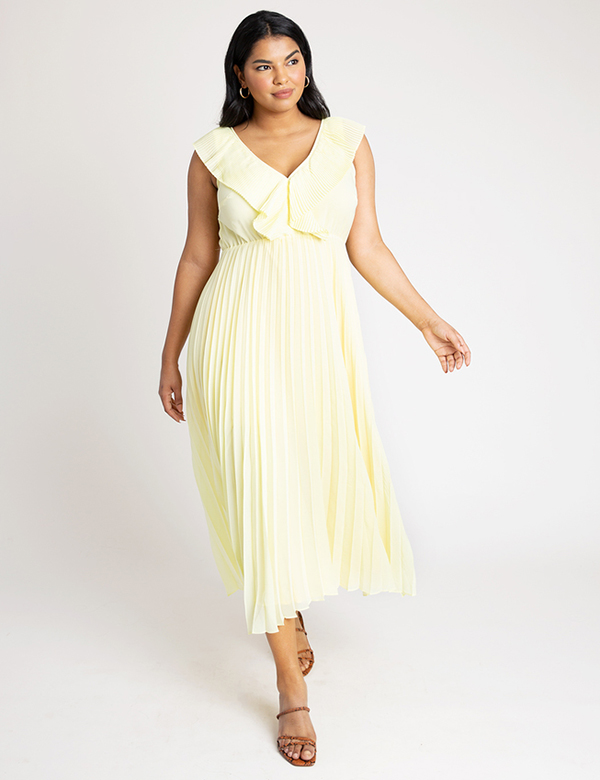 A plus-size model wearing a pale yellow ruffled dress, which is now on sale at Eloquii for less than $49.