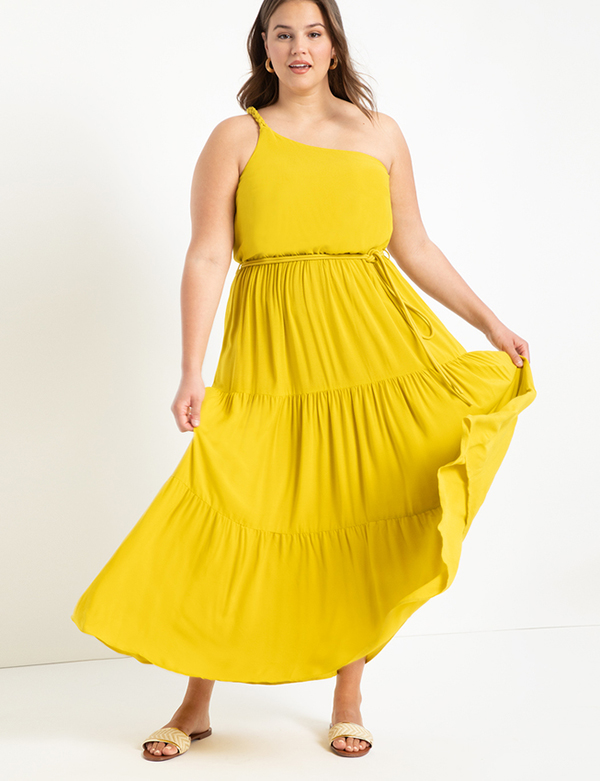 A plus-size model wearing a one-shoulder yellow dress, which is now on sale at Eloquii for less than $49.