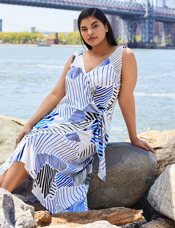 A plus-size model wearing a blue printed wrap dress, which is now on sale at Eloquii for less than $49.