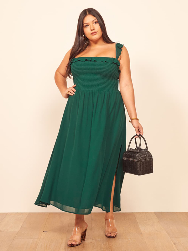 A plus-size model wearing a green maxi dress, which are currently on sale at Reformation.