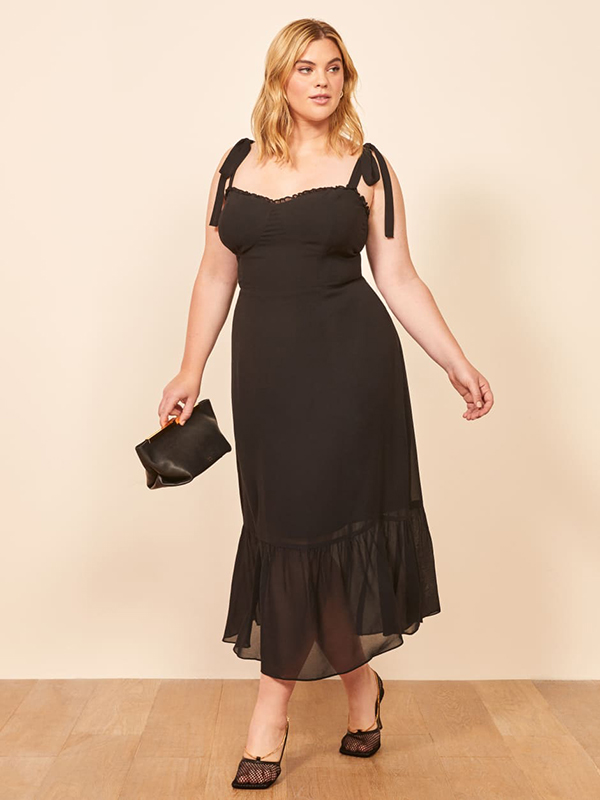 A plus-size model wearing a black dress, which are currently on sale at Reformation.