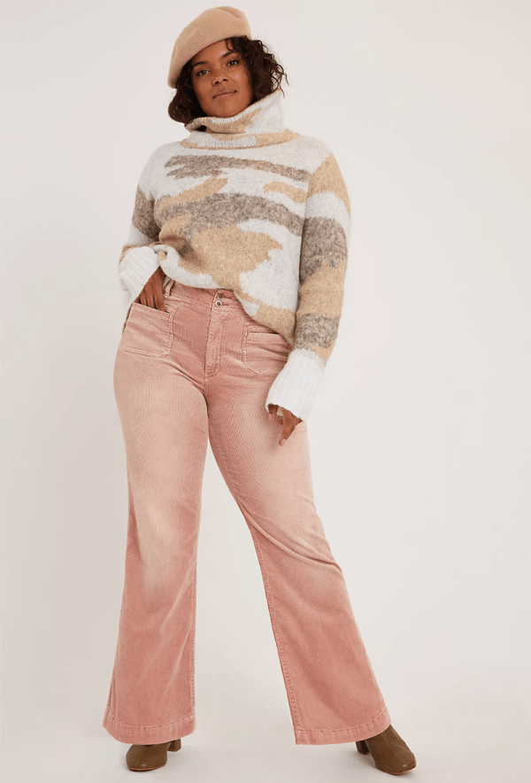 A plus-size model wearing pink corduroy pants.