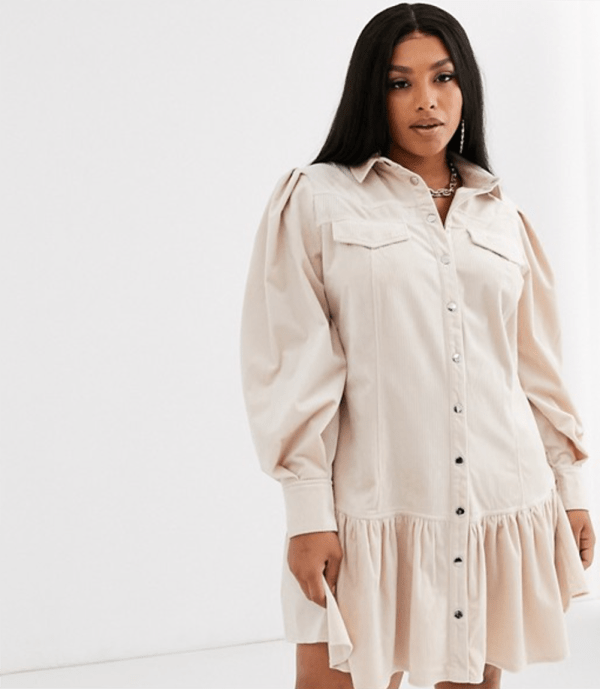 A plus-size model wearing a beige corduroy shirtdress.