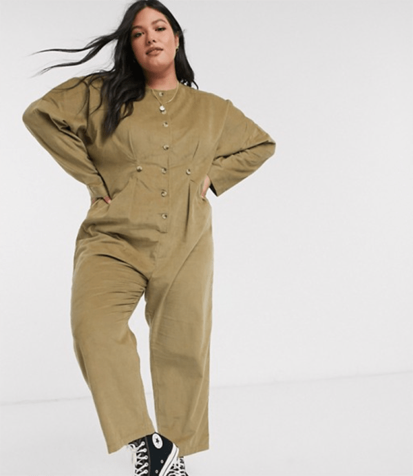 A plus-size model wearing an olive green corduroy jumpsuit.