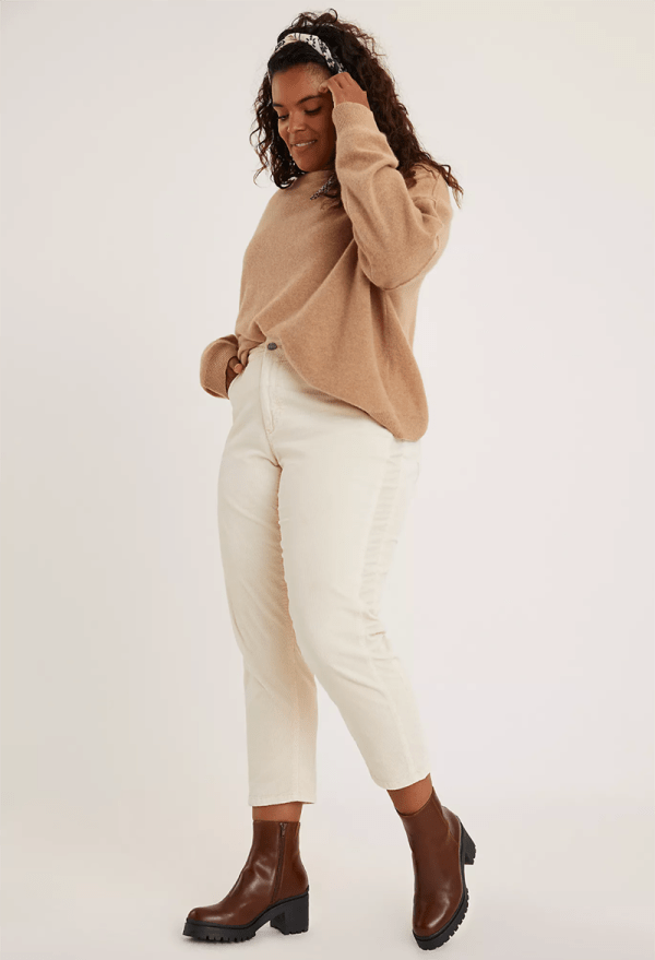 A plus-size model wearing white corduroy pants.