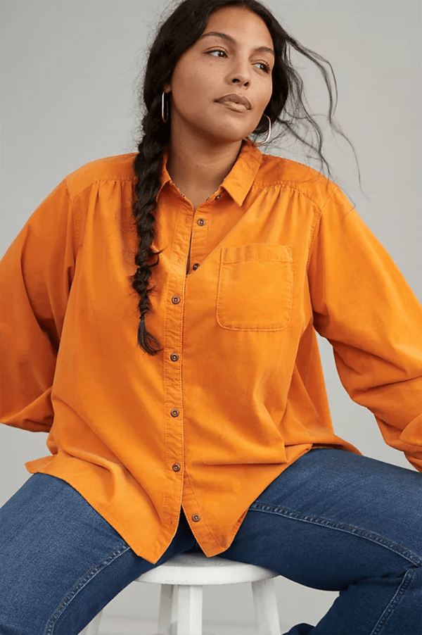 A plus-size model wearing an orange corduroy shirt.