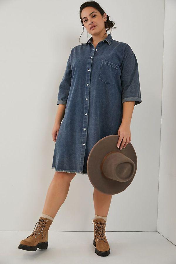 A plus-size model wearing a button-up denim dress.