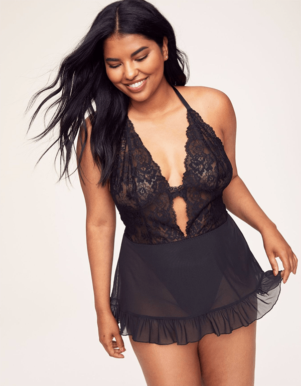 A plus-size model wearing black lace lingerie teddy, which is currently on sale at Adore Me.