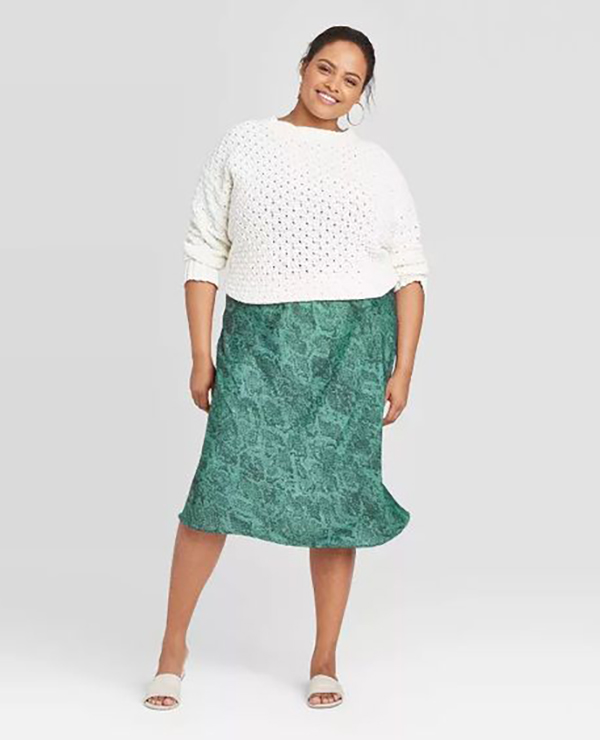 A plus-size model wearing a teal, snake print, satin midi skirt.