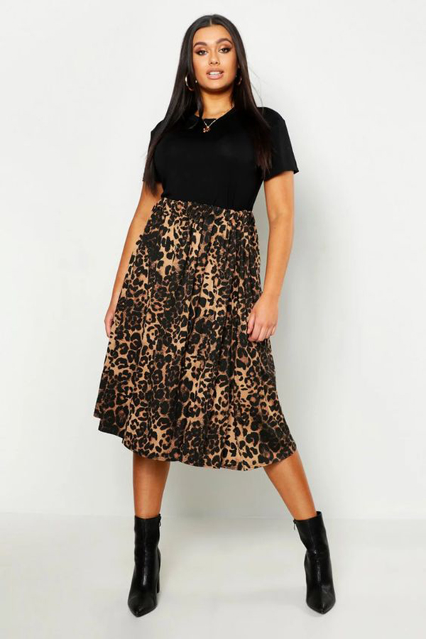 A plus-size model wearing an animal print, pleated midi skirt.