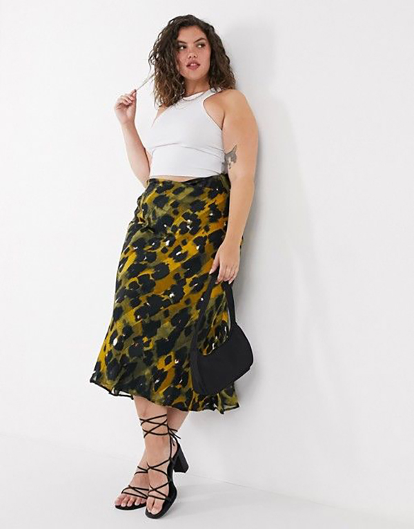 A plus-size model wearing a printed, satin midi skirt.