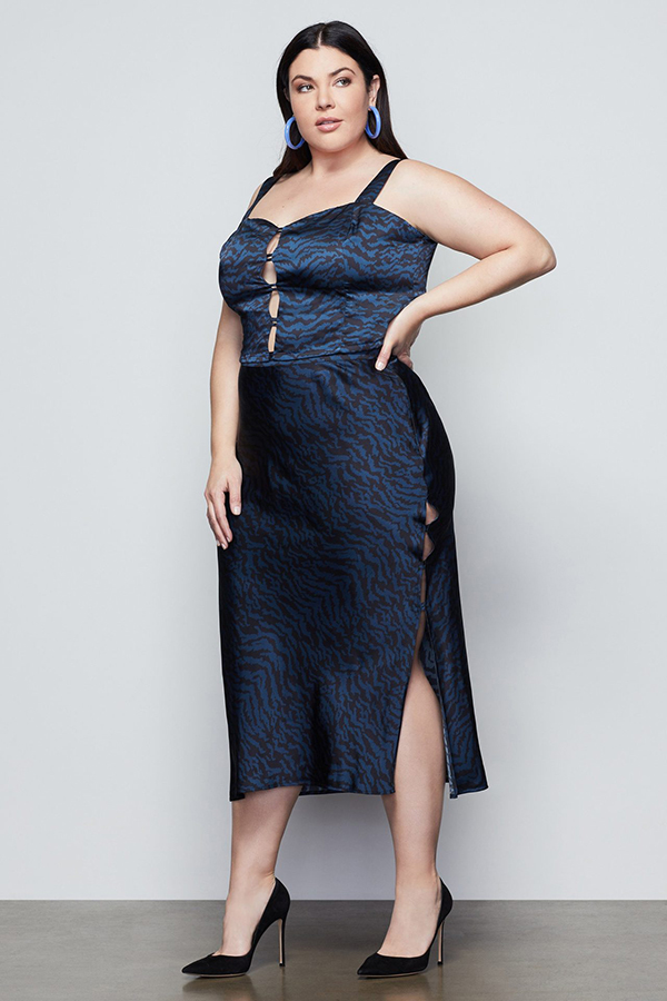 A plus-size model wearing a navy, animal print midi skirt.