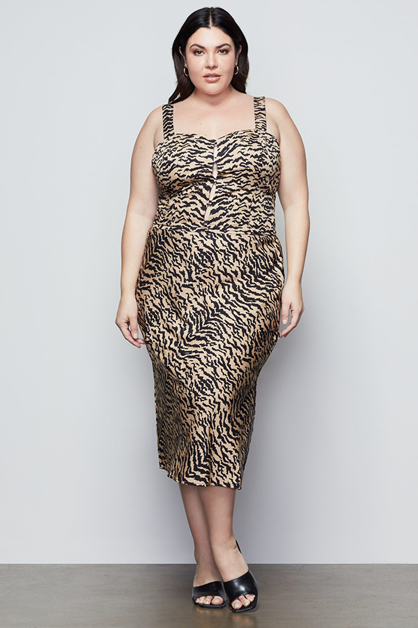 A plus-size model wearing an animal print midi skirt.