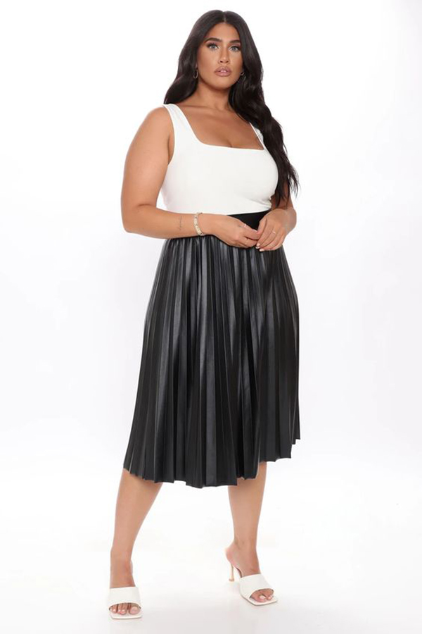 A plus-size model wearing a black leather, pleated midi skirt.