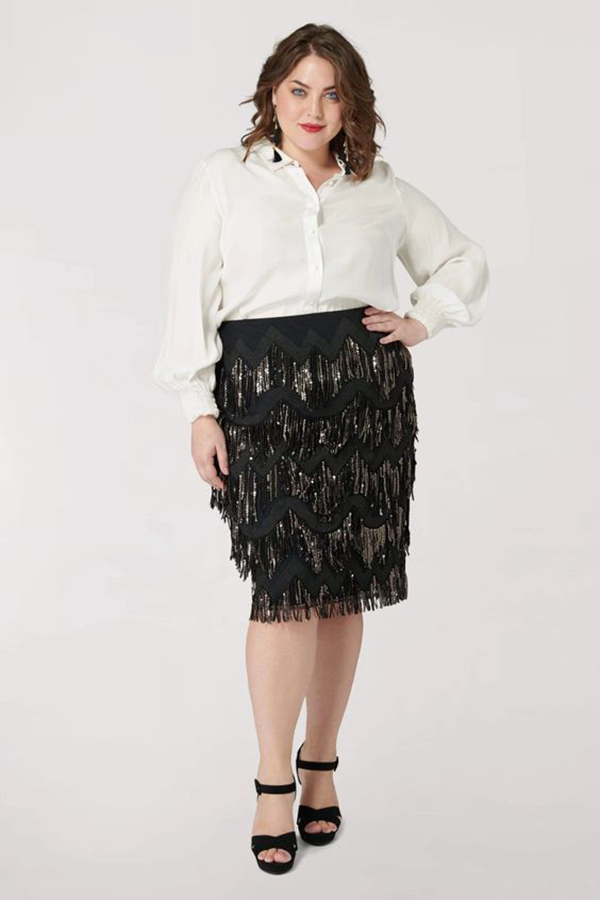 A plus-size model wearing a black, sequin-fringe midi skirt.